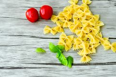Raw farfalle. Close up of  row farfalle pasta on   wooden background  .wirh cherry tomatoes and fresh basil .Italian healthy food background. View from above Royalty Free Stock Photography