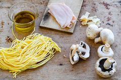 Italian   pasta ingredients. Close up of  row fresh  spaghetti alla chitarra pasta , parmesan cheese, ham  and olive iol  Italian healthy food background. View Stock Images