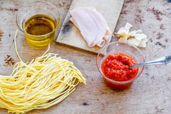 Italian Food ingredients. Close up of  row fresh   Spaghetti Pasta , Parmesan cheese,  home made  tomato paste  , Olive oil , Chichken Ham  and  Mushrooms Royalty Free Stock Images
