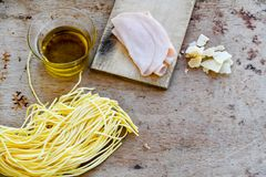 Italian Food ingredients. Close up of  row fresh   Spaghetti Pasta , Parmesan cheese,   , Olive oil , Chichken Ham  and  Mushrooms .spaghetti and ingredients Stock Photography