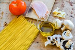 Italian Food ingredients. Close up of  row fresh   Spaghetti Pasta , Parmesan cheese,   fresh Tomato, Olive oil , Chichken Ham  and  Mushrooms .spaghetti and Royalty Free Stock Image