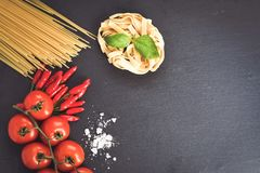 Fresh pasta ingredients. Close up of  row  fresh  spaghetti pasta and tagliatelle pasta , fresh basil   tomatoes, chili peppers and salt on black slate.spaghetti Stock Photo