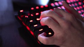 Close-up On Row of Gamer`s Hands on a Keyboards, Actively Pushing Buttons, Playing MMO Games Online. Background is Lit stock video footage