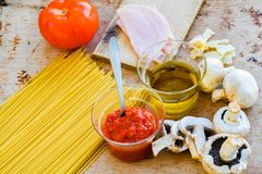 Italian Food  ingredients. Close up of  row   spaghetti pasta , parmesan cheese,     fresh tomato, olive oil extra vergin, ham  and  mushrooms .spaghetti and Stock Image