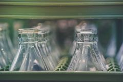 Close up row of used soft drink glass bottles in green container in vintage style. Selective focus Royalty Free Stock Photo