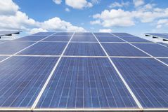 Close up rows array of polycrystalline silicon solar cells or photovoltaics in solar power plant alternative renewable energy from. The sun on blue sky Stock Images