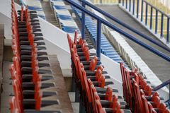 Rows of red , blue and white folding chairs in the football stadium royalty free stock photos
