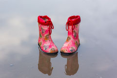 Close-up of rubber boots in a puddle on a rainy day. Pair of rubber boots in a puddle Stock Photos