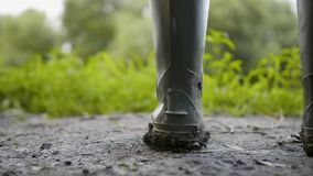 Close up rubber rain boot with mud work on dirty place.  stock video footage