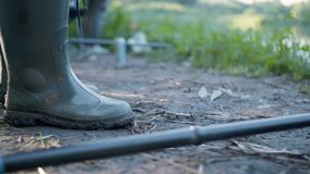 Close up rubber rain boot with mud work and rod on dirty place.  stock video footage