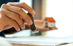 Home mortgage business concept,Close-up rubber stamp and model h. Close-up rubber stamp and model house in hand,Concept image of home mortgage business Royalty Free Stock Photos
