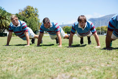 Close up of rugby players doing push up at field. On sunny day Royalty Free Stock Images