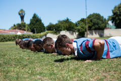 Close up of rugby players doing push up. At grassy field on sunny day Royalty Free Stock Photos