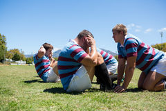 Close up of rugby players exercising on grassy field Stock Photography