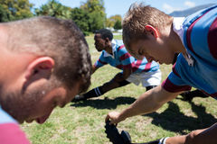 Close up of rugby players stretching at field Royalty Free Stock Images