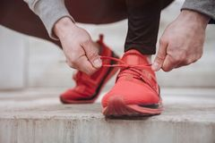 Tying up shoelaces. Close up of a man tying up his shoelaces before the run with copy space royalty free stock photo