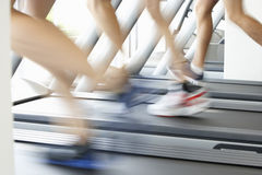 Close Up Of 3 Runners Feet On Running Machine In Gym Stock Photo