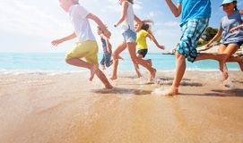 Close-up of running kids legs in shallow sea water Stock Images