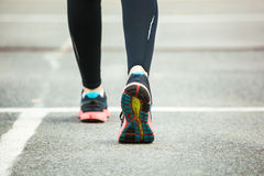 Close up of running shoes on road. Royalty Free Stock Images