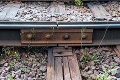 A close-up of rust metal rivets. Old sleepers, in city there is a tram line. In nature, a wet wooden board. Coupling of Royalty Free Stock Images