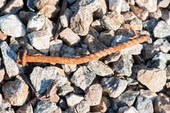 Close up of rusted railroad track spike. Close up of railroad track spike with rocks stock photo