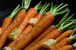 Close up of rustic carrotts in a pan with butter on wood Stock Images