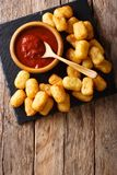 Close up of rustic golden potato tater tots and ketchup. Vertica. Close up of rustic golden potato tater tots and ketchup on the table. Vertical top view from Stock Photo