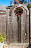 Close-up of rustic wooden gate with decorative round wrought iron window and a planting trowel for a knocker with two story house stock images