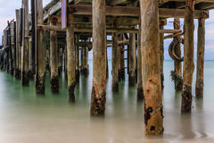 Close up of rustic wooden jetty in the sea. Close up of rustic wooden jetty extending into the sea Stock Photography