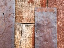 Close up of rustic wooden wall with rusty metal plates royalty free stock images