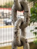 Close up of rusty chain links in the foreground. Close up of rusty chain links in foreground, with grid on background Royalty Free Stock Photos