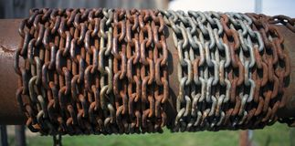 Rusty chain wrapped around tube on old water well stock image