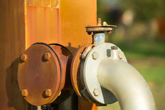 Close up Rusty old energy supply pipeline pump. Close up rustic colored pump pipeline with elbow pipe and old valve for residential energy supply, blurred Stock Photos