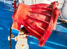 Close-up of a rusty red color painted flood light on a ship stock image