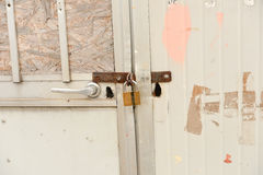 Close up of rusty steel door securely locked with a golden pad Stock Images