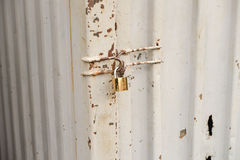 Close up of rusty steel door securely locked with a golden pad Stock Photo