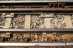Close-up of rusty train track with railroad tie and pebbles, horizontal. Close-up of rusty train track with railroad tie and pebbles in a rural area of Thailand royalty free stock images
