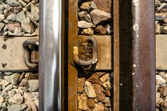 Close-up of rusty train track with railroad tie and pebbles, vertical. royalty free stock images