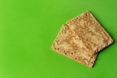 Close-up of rye crackers with butter - on bright green backgroun royalty free stock photo