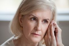 Close up of sad aged woman lost in thoughts royalty free stock image