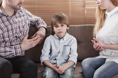 Sad child while parents arguing. Close-up of sad child and his parents arguing. Problem in the family concept stock photos