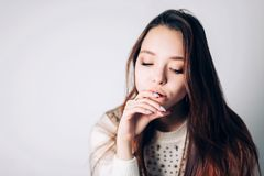 Close-up of a sad and depressed woman on white background. Beautiful girl without sentiment looks down. Close-up of a sad and depressed woman on white Stock Image