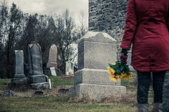 Close-up of a Sad in front of a Gravestone. Close-up of a Sad Woman Holding Sunflowers in front of a Loved one's Gravestone. Focus on the Grave Royalty Free Stock Image