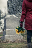 Close-up of a Sad in front of a Gravestone. Close-up of a Sad Woman Holding Sunflowers in front of a Loved one's Gravestone. Focus on the Grave royalty free stock images
