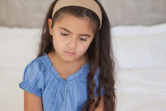 Close-up of a sad girl sitting on bed Stock Images