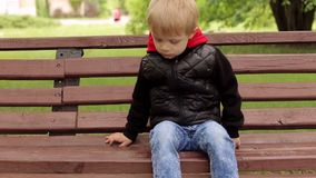 Portrait of a sad boy in the Park on a bench. Close-up of a sad little boy of five years in a black jacket sitting on a bench in a park, the background is stock video