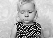 Close up sad little girl. Eyes are lowered, black and white Royalty Free Stock Images