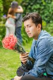 Close up of sad man wearing a jean jacket and black pants sitting in the ground holding flowers in his hands, with a. Blurred couple behind embracing each other Stock Image