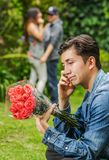 Close up of sad man wearing a jean jacket and black pants sitting in the ground holding flowers in his hands, with a. Blurred couple behind embracing each other Royalty Free Stock Photo