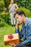 Close up of sad man wearing a jean jacket and black pants sitting in the ground holding gift with a blurred woman behind. Using her cellphone. Valentine`s Day Royalty Free Stock Photography